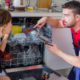 Plumber installing new dishwasher and explaining to housewife