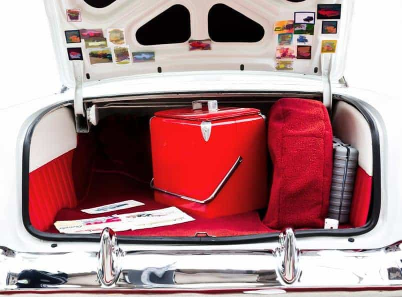An open classic car trunk with red cooler inside