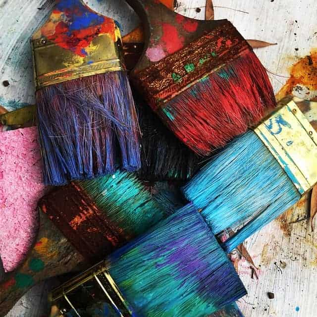 Large paint brushes filled with purple, blue, and red paint