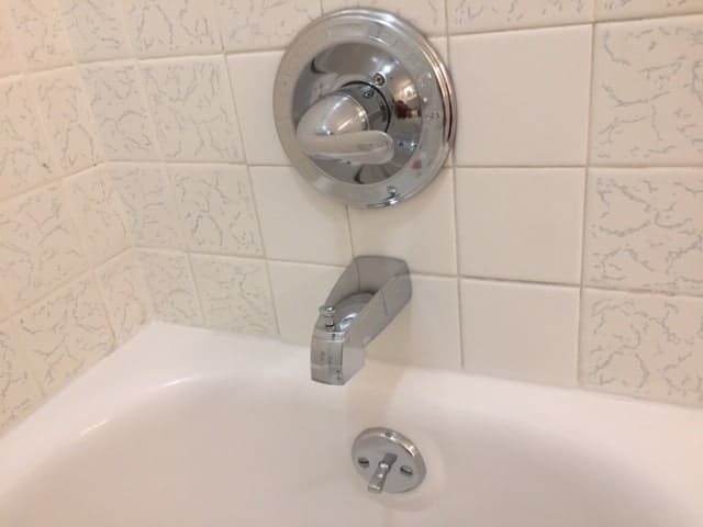 A tiled bathtub with chrome faucet and temperature control