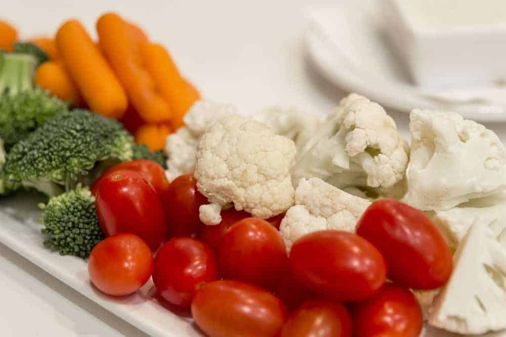 A plate full of raw carrots, broccoli, cauliflower, and cherry tomatoes