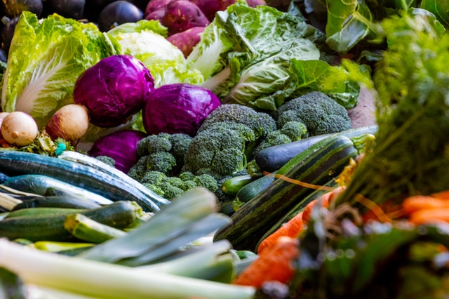assorted collection of brightly colored veggies including cabbage, onions and peppers
