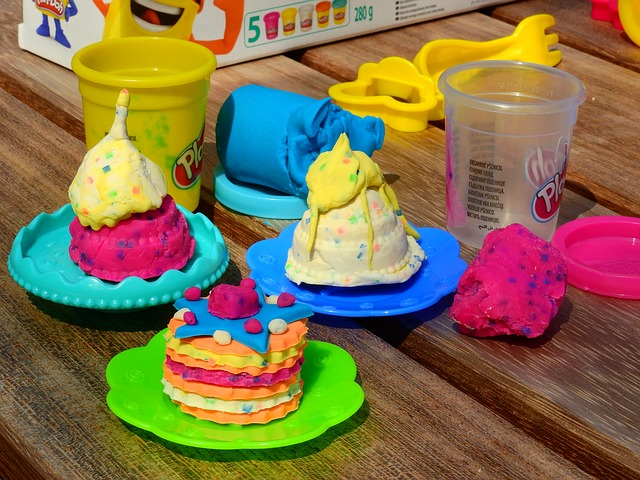 table filled with colorful play dough creations in the shape of foods such as pancakes and ice cream sundaes