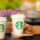 two Starbucks coffee cups - one being held in a person's hand and the other sitting on the table