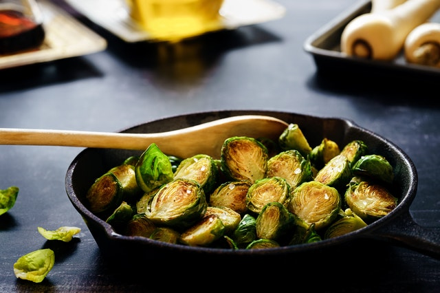 cast iron skillet full of browned Brussel sprouts