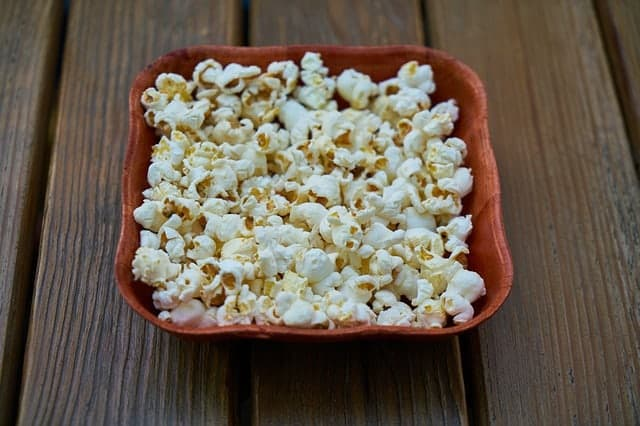 Food on a wooden cutting board, with Popcorn