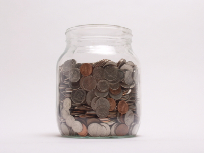glass jar mostly filled with U.S. coins