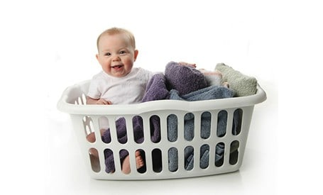 laundry basket holding towels and a baby!
