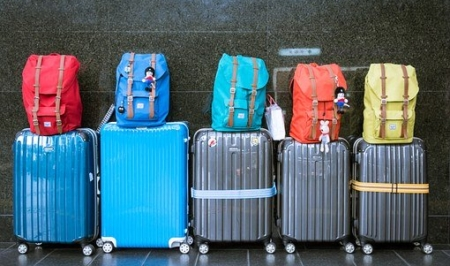 A pile of luggage sitting on top of a suitcase