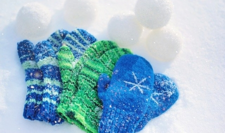 three sets of kids mittens lying in the snow with stacks of snowballs in the background