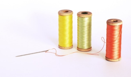 3 spools of thread and a sewing needle