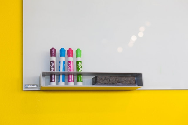 the lower corner of a blank whiteboard with several markers and an eraser neatly arranged in front of it.