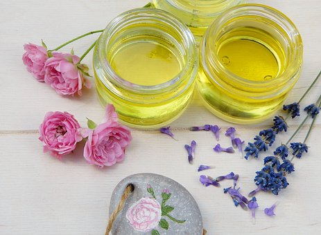 Two jars of oil oil surrounded by pink flowers and fresh lavender