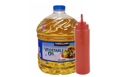 gallon of vegetable oil next to a red slim condiment bottle
