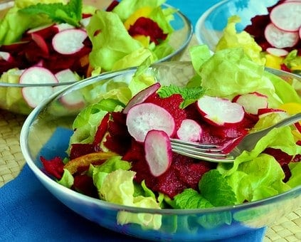 Three bowls of salad greens with raw turnips