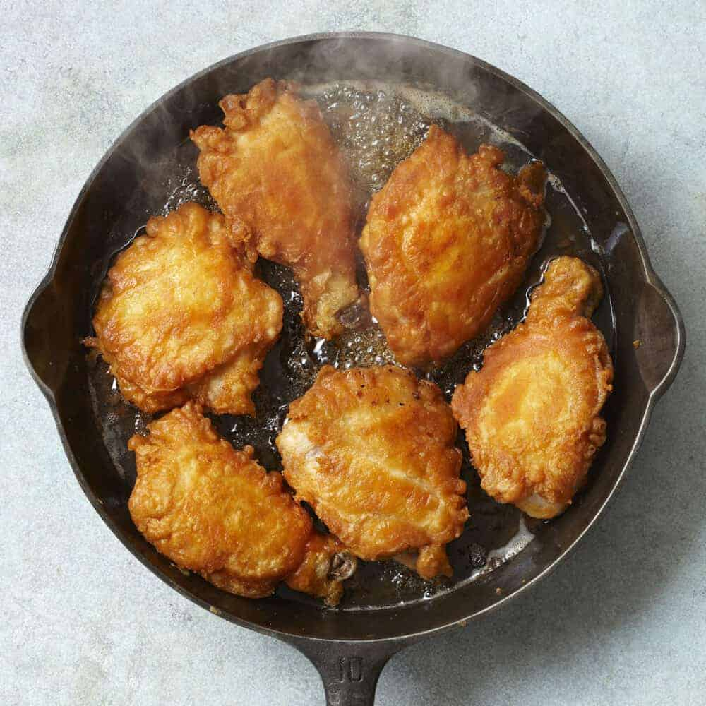 Fried chicken cooking in a cast iron skillet