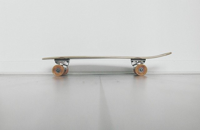side view of a generic skateboard on a shiny concrete floor