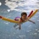 picture of young girl in a pool draping her arms over a pool noodle