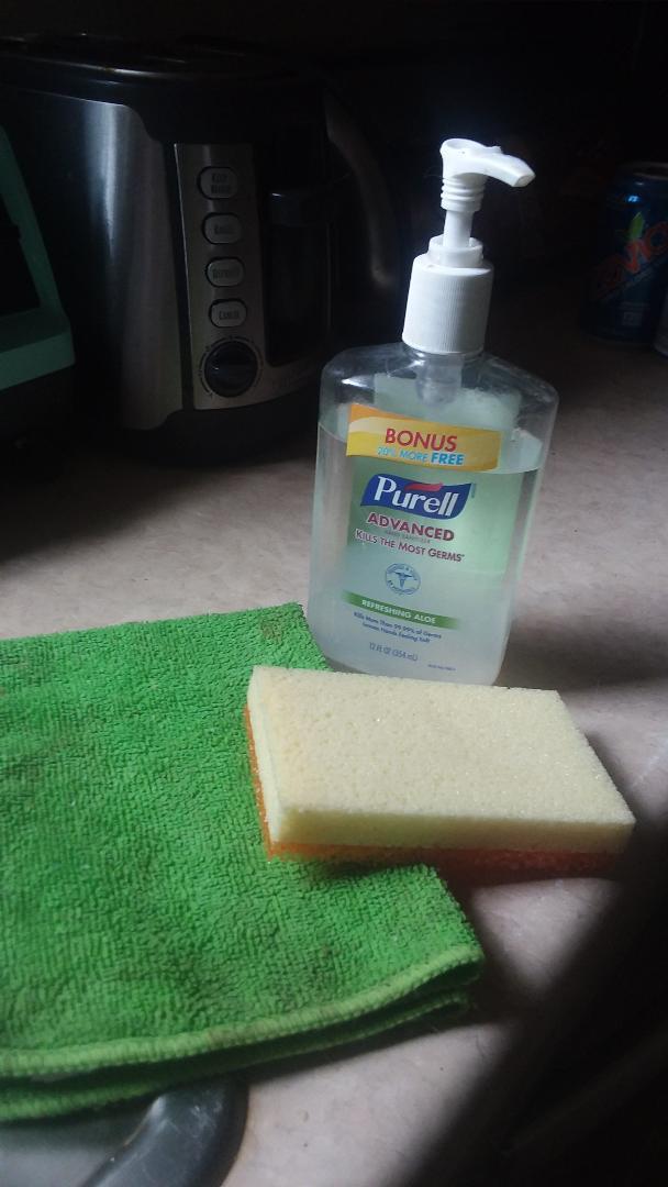 microfiber towel, sponge and bottle of hand sanitizer