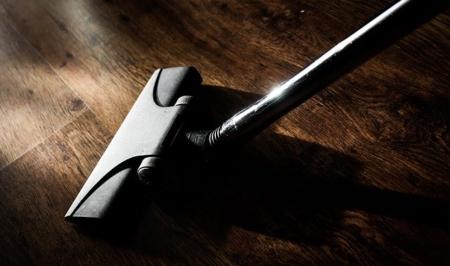 head of vacuum cleaner on a wood floor in dim light
