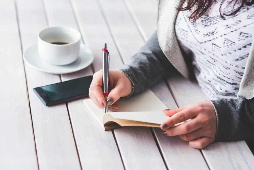 Woman writing with a pen and paper